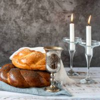 Shabbat Shalom - challah bread, shabbat wine and candles on grey background. With copy space.